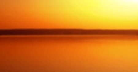 orange sunset: very blurred background, orange sunset reflecting in the water Stock Photo
