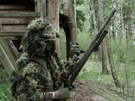 robustness: airsoft player with Ghillie Suit and sniper rifle