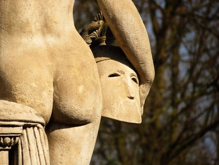 anthropomorphous: detail of the back of the sanstone statue with white buttocks and helmed, dark background Stock Photo