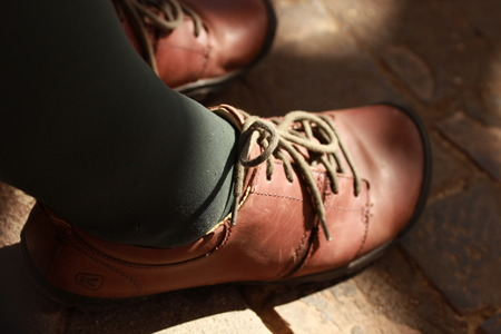 placed: Detail of lower leg, laces on old worn brown leather shoes. Boots are placed on brown background. Vintage, retro old time design Stock Photo