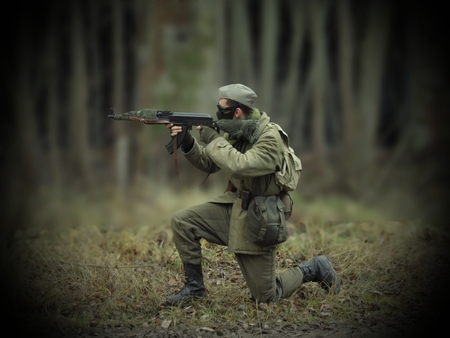 rifleman: Masked airsoft player, who plays for Russian side of the army, old time scenery, blurred blackground, dark vigneting