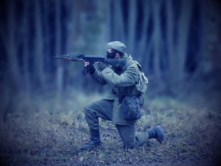 rifleman: Blue Masked airsoft player, who plays for Russian side of the army, old time scenery, blurred blackground, dark vigneting