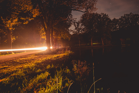 night drive through the woods with a car, a light footprint captured