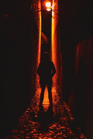 a mysterious photograph of a man standing between two narrow walls