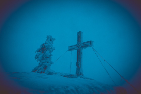 cross on top of the mountain, dark cloudy weather and great strong wind