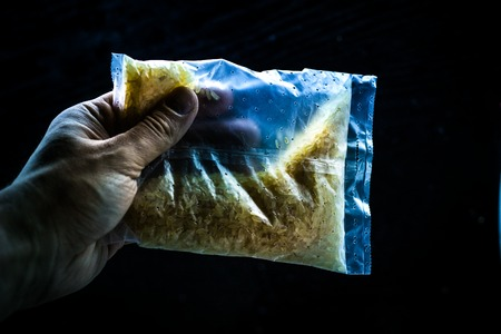 the Hand holding natural raw rice in plastic bag 写真素材