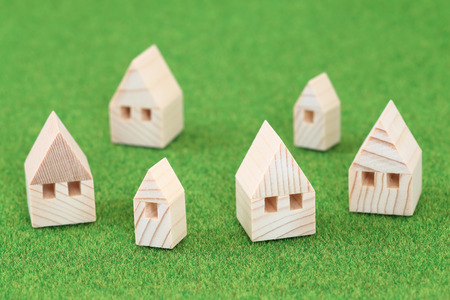domiciles: Miniature house on green background