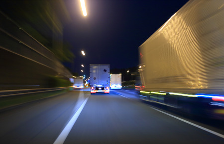 Truck driving on highway at night Stock Photo