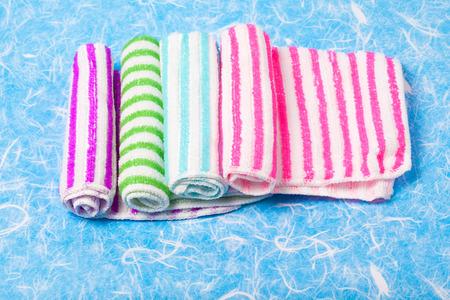 dishtowel: Roll napkin fabric hand on background.