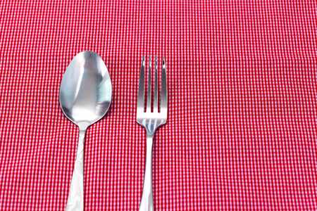 fabrick: Silver fork and spoon on red fabrick. Selective focus.
