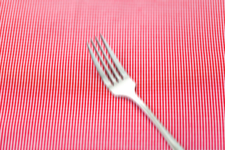 fabrick: Abstract blur Silver fork and spoon on red fabrick. Selective focus.