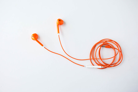 earphone: Orange color earphone on background. Stock Photo