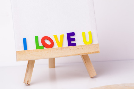 wooden easel, front view with word I Love You Creative Motivation Quote. Stock Photo