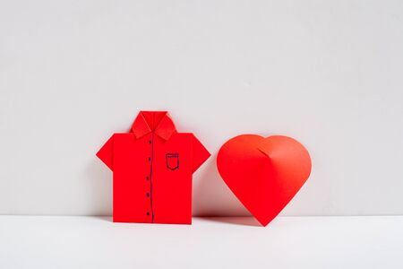 Red shirt origami with red heart on white background. Stock Photo