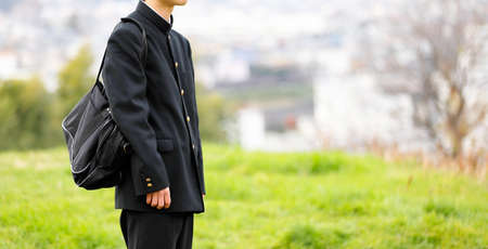 A high school student standing alone