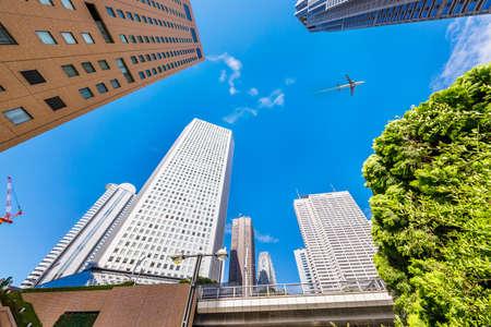 Nishi-Shinjuku high-rise buildings and airplanes with beautiful fresh green
