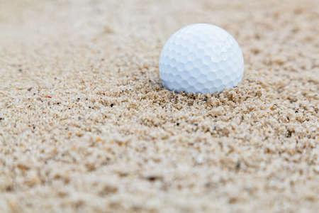 Golf ball in bunker Фото со стока