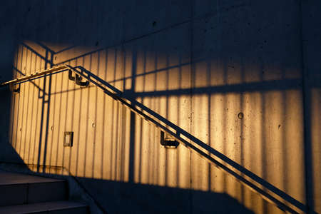 Outside stairs and railings illuminated by orange sunset light Standard-Bild