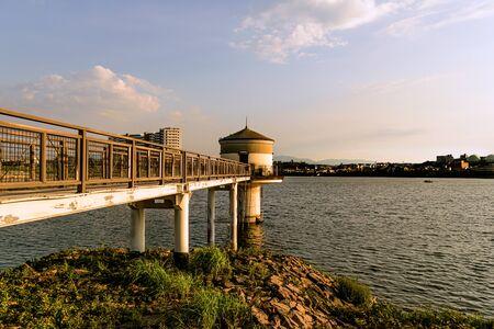 Pier at Sayama Pond in Osaka, Japan, illuminated by the setting sun