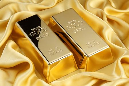 barra: Barras de oro en la seda de oro Foto de archivo