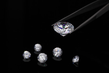 round brilliant: Diamond jewelry holding round brilliant cut diamond held in tweezers Stock Photo