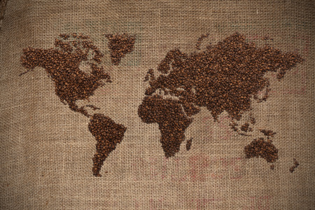 Wold map made of coffee beans on textured background