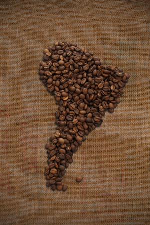 South America continent map made from coffee beans on jute background