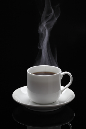 Cup of black coffee with steam on the black background
