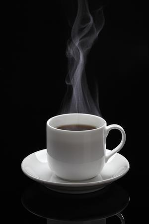 Kopje zwarte koffie met stoom op de zwarte achtergrond Stockfoto