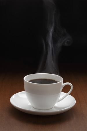 木製のテーブルの上に蒸気とブラックコーヒーのカップ