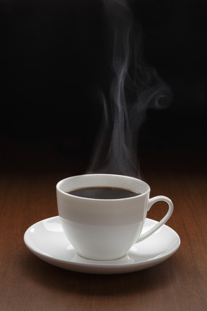 Cup of black coffee with steam on the wooden table Stock Photo