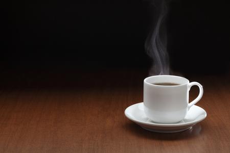 Tazza di caffè nero con vapore sul tavolo di legno