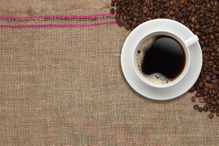 grano de cafe: Granos de café y taza de café sobre un fondo de yute