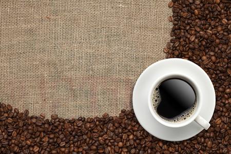 コーヒー豆、ジュート バック グラウンドでコーヒー カップ