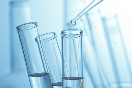 research science: Liquid drop from laboratory glass pipette to test tube Stock Photo