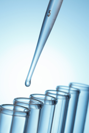 test: Liquid drop from laboratory glass pipette to test tube Stock Photo