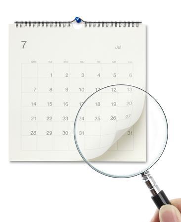 lupa: Mano que sostiene una lupa para comprobar el calendario