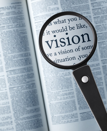 single word: VISIONMagnifying glass on the vision in dictionary