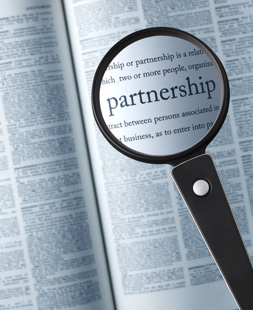 single word: PartnershipMagnifying glass on the partnership in dictionary