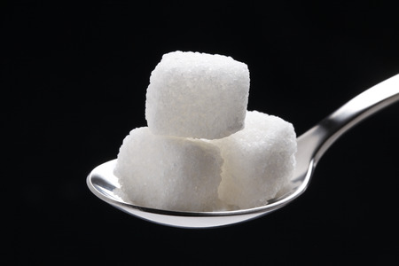 the cubes of white sugar in a silver spoon, isolated on black Stock Photo
