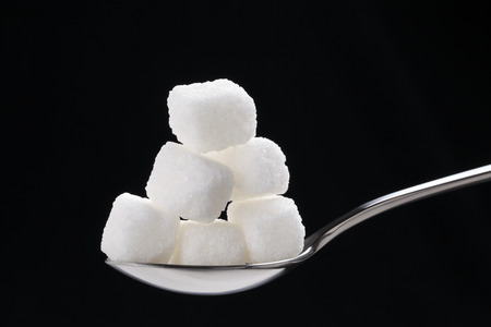 over black: the cubes of white sugar in a silver spoon, isolated on black
