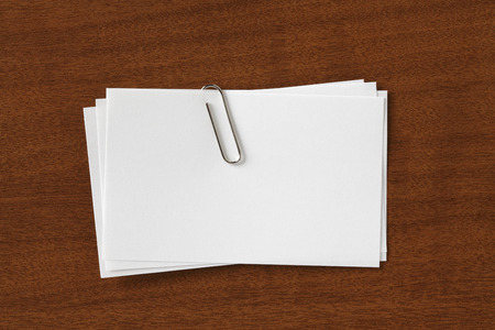 stack of paper: Stack of Blank Cards with paper Clip. on Wood Desk Stock Photo
