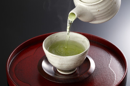 Japanese green tea in porcelain cup and tea pot.