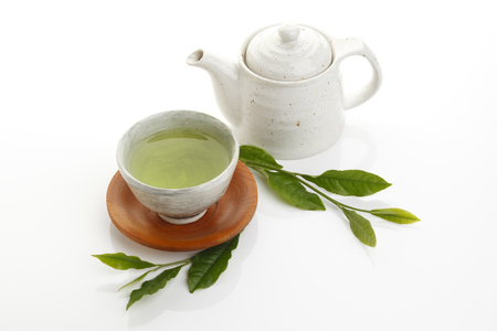 green herbs: Japanese green tea and fresh green tea leaves with teapot on white background