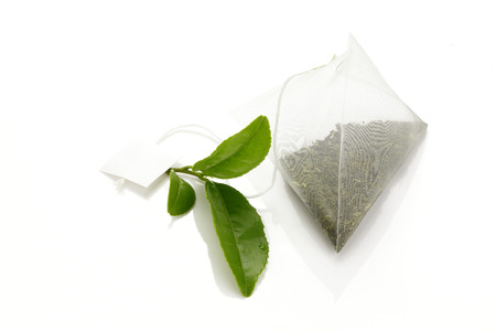 teabag: Green tea Teabag and fresh green tea leaves Stock Photo