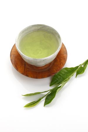 japanese green tea: Japanese green tea and fresh green tea leaves on white background