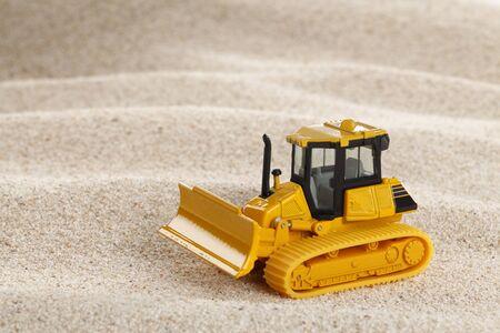 earthing: Heavy crawler toy bulldozer on sand dune