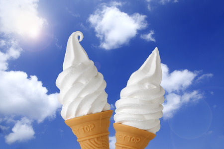 A cone of vanilla ice-cream on a hot summer day