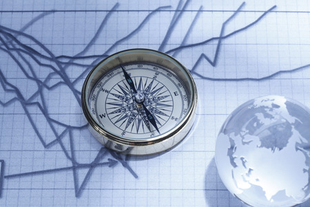 Close-up of a compass on stock market data chart with crystal globe