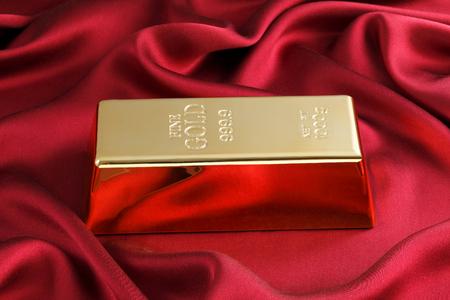 lingote de oro: Foto de una barra de 1 kg de oro en el sat�n rojo Foto de archivo